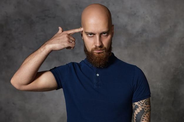 Jesteś szalony czy głupi? zirytowany, poirytowany młody brodaty mężczyzna w koszulce polo toczy palcem wskazującym na jego skroni. szalony, wściekły mężczyzna z zarostem, wykonujący gest samobójczy z powodu nudnej rozmowy