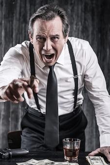 Jesteś trupem! wściekły starszy mężczyzna w koszuli i szelkach krzyczy i wskazuje cię, opierając się o stół z dużą ilością pieniędzy leżących obok niego