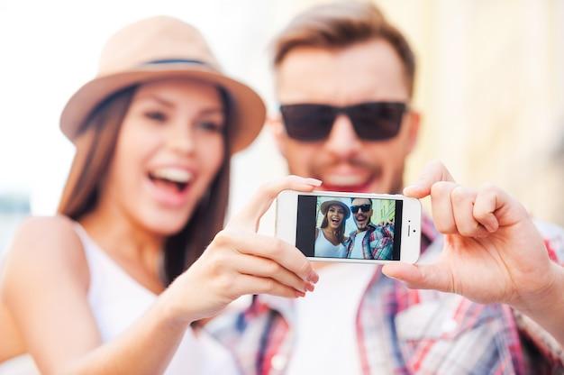 Jesteśmy piękni! szczęśliwa młoda para kochająca robi selfie stojąc razem na zewnątrz