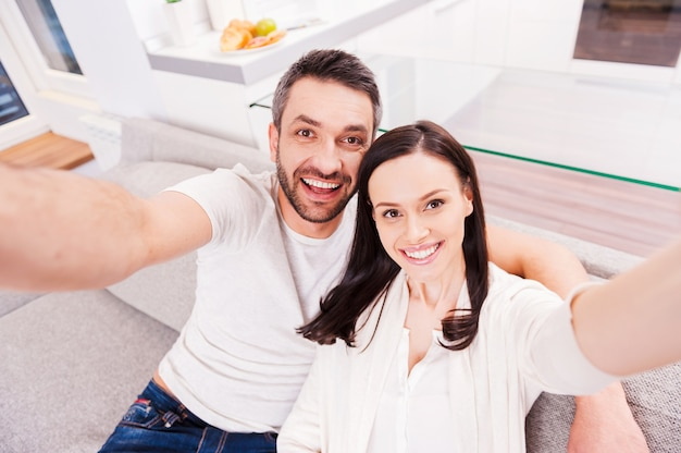 Jesteśmy piękni! widok z góry na szczęśliwą, kochającą się parę, która łączy się ze sobą i robi selfie, siedząc razem na kanapie