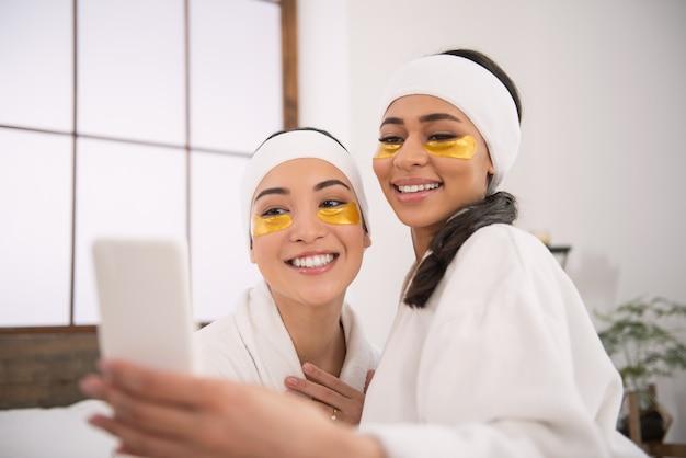 Jesteśmy piękni. zachwycone szczęśliwe kobiety noszące opaski na oczy i robiące im wspólne zdjęcie