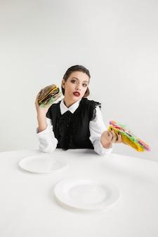Jesteśmy tym co jemy. kobieta je burgera i hot-doga z tworzywa sztucznego, koncepcja eko