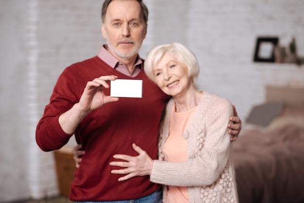 Jesteśmy ubezpieczeni. całkiem starsza kobieta obejmując jej męża trzymając podczas gdy karta ubezpieczenia społecznego.