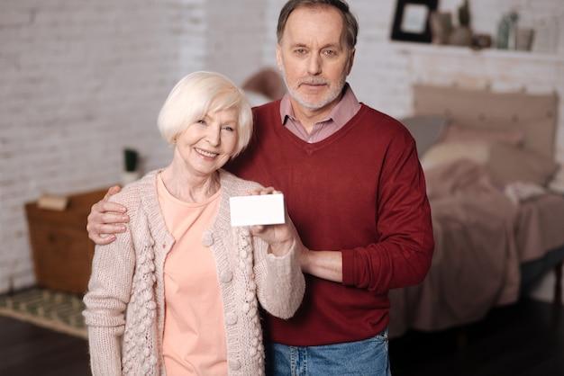 Jesteśmy zabezpieczeni. starsza rodzina stoi w domu i kobieta trzyma nową kartę ubezpieczeniową.