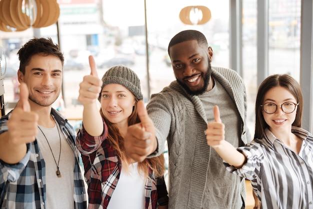 Jesteśmy zwycięzcami. grupa młodych szczęśliwych studentów zagranicznych stoi i kciuki w górę.