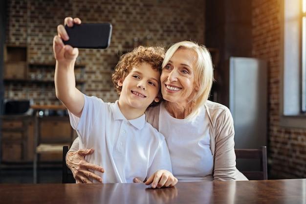 Jeszcze jeden kieliszek. rozpromieniona starsza pani obejmująca swojego wnuka, który nie miał już lat, siedząc przy stole i robiąc selfie, spędzając razem trochę czasu.