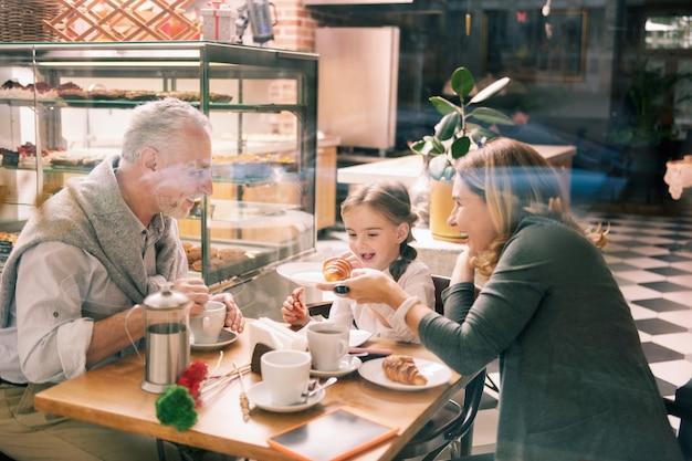 Jeszcze jeden rogalik. ciemnowłosa śliczna wnuczka prosi o jeszcze jednego rogalika na śniadaniu z rodziną