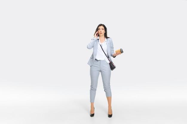 Jeszcze minuta i jesteś zwolniony. młoda kobieta w szarym garniturze dostaje szokujące wieści od szefa lub współpracowników. wyglądał na odrętwiałego podczas upuszczania kawy. pojęcie kłopotów pracownika biurowego, biznesu, stresu.