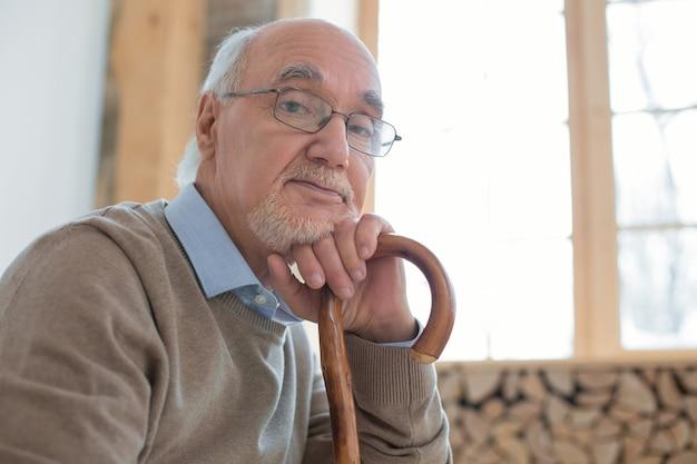 Jeszcze minuta. ładny przystojny starszy mężczyzna patrząc na kamery, opierając się na lasce i nosząc okulary