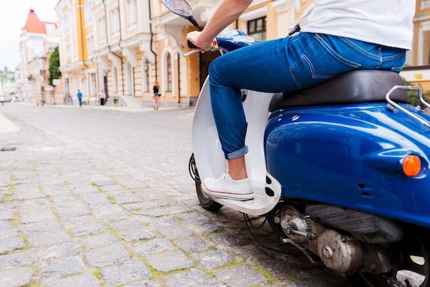 Jeździ na swoim nowym skuterze. widok z tyłu przycięty obraz młodego mężczyzny jadącego skuterem wzdłuż ulicy