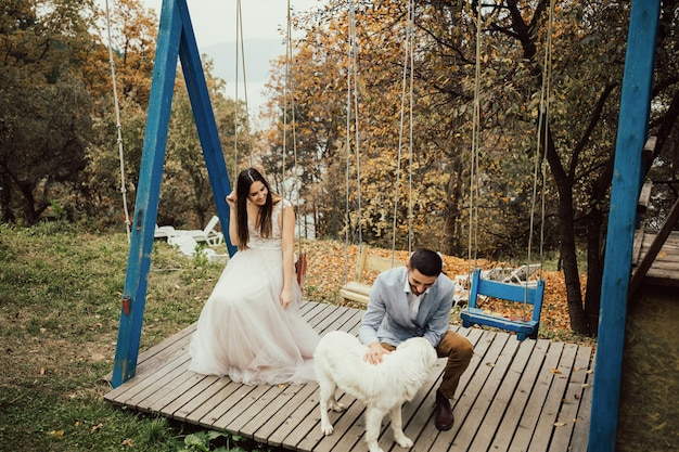 Jeździć i pan młody na huśtawce na rustykalnym jesiennym weselu.