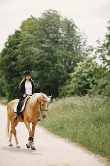 Jeździec kobieta jedzie na koniu na ranczo. kobieta ma długie włosy i czarne ubrania. kobieta jeździecka na swoim brązowym koniu.