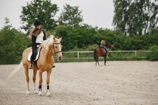 Jeździec kobieta jedzie na koniu na ranczo. kobieta ma długie włosy i czarne ubrania. niewyraźne drugi jeździec na koniu na tle.