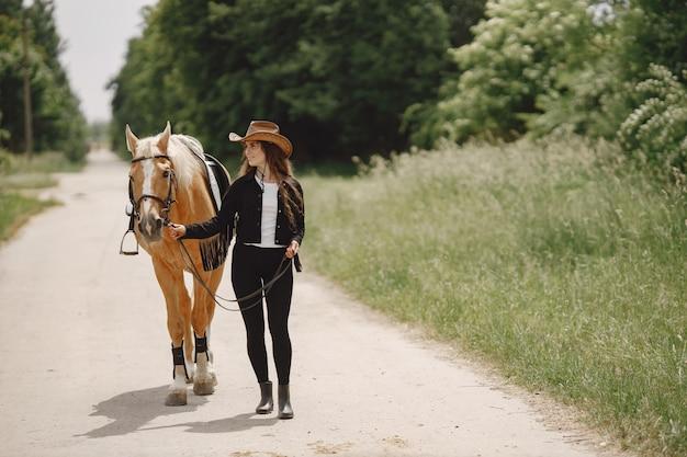 Jeździec kobieta spaceru z koniem na drodze. kobieta ma długie włosy i czarne ubrania. kobieta jeździectwo trzyma wodze konia.
