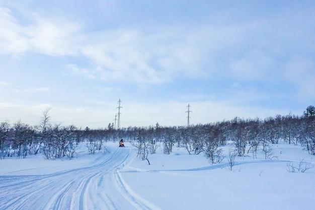 Jeździec na skuterze śnieżnym w górach ośrodek narciarski w amur w rosji.