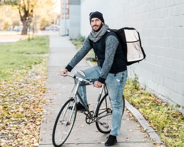 Jeździec na wynos pozuje z rowerem i torbą z jedzeniem.