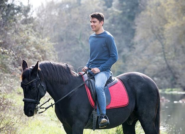 Jeździec trenuje swojego czarnego konia