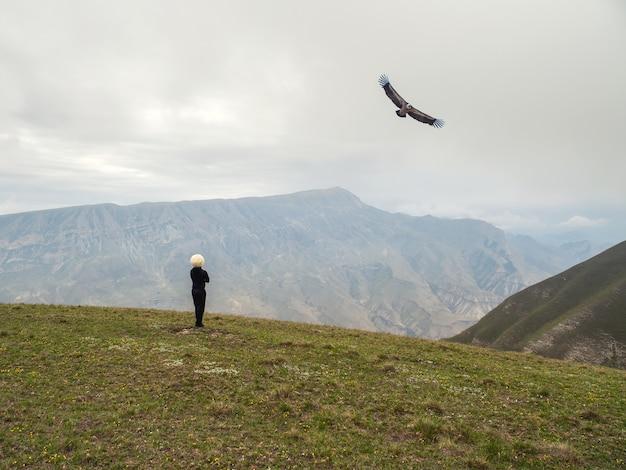 Jeździec w białej czapce i orła w locie na tle wysokich gór.