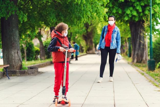 Jeździecka chłopiec na hulajnoga w parku. chłopiec nosi maski medyczne. matka i syn na spacerze