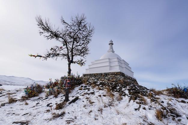 Jeziorny bajkał rosja, marzec, - 10, 2020: buddyjska stupa przy ogoy wyspą na baikal jeziorze. ogoy to największa wyspa na cieśninie maloe more jeziora bajkał.