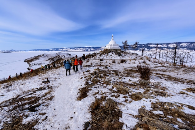 Jeziorny bajkał rosja, marzec, - 10, 2020: tłumy turyści chodzą wokoło buddyjskiej stupy przy ogoy wyspą na bajkał jeziorze. ogoy to największa wyspa na cieśninie maloe more jeziora bajkał.