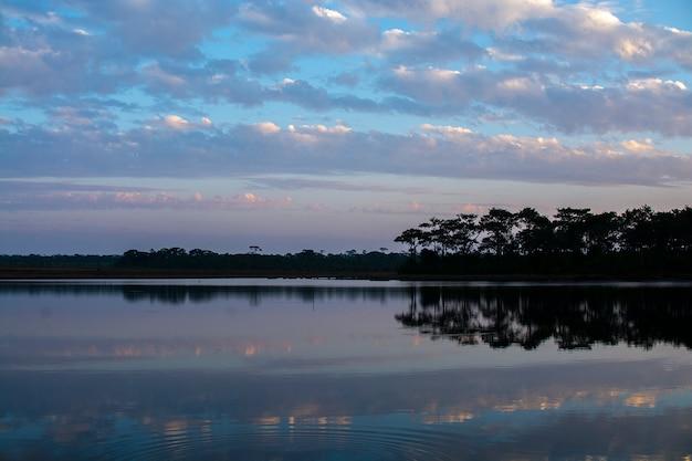 Jeziorny widok przy zmierzchu czasem z chmurami na niebie