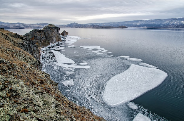Jezioro bajkał i rock w grudniowym chłodzie. czas zamrożenia. kry pływa na wodzie