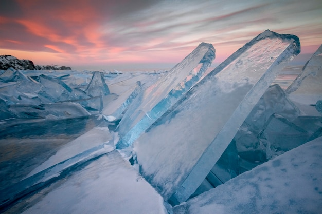 Jezioro bajkał o zachodzie słońca, wszystko pokryte jest lodem i śniegiem, gęsty, przezroczysty niebieski lód. jezioro bajkał w promieniach zachodzącego słońca.
