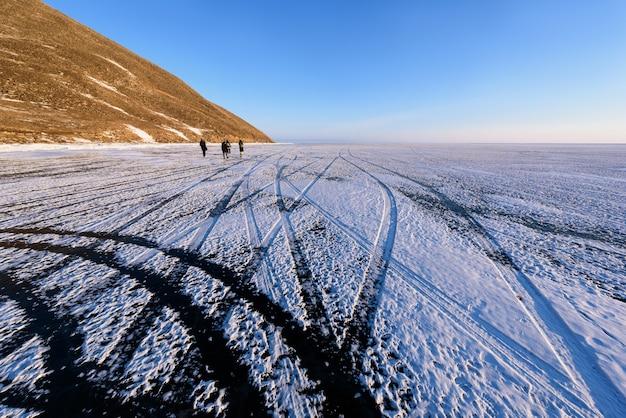 Jezioro bajkał zimą powierzchnia jeziora jest zamarznięta, tak mocna, że może przejechać pojazd. ślady opon na lodzie