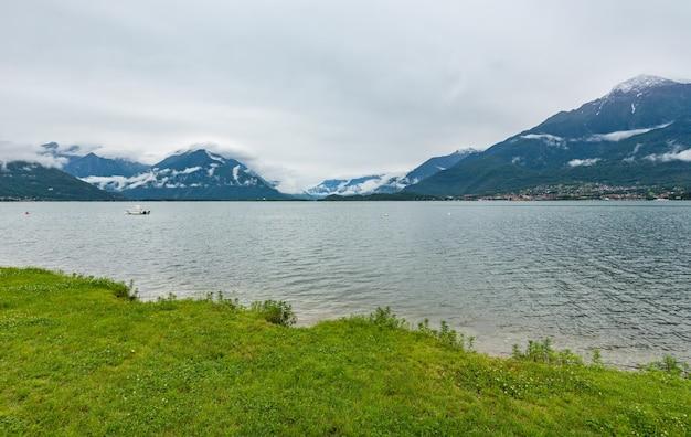 Jezioro como (włochy) latem pochmurny widok ze śniegiem na szczycie góry.