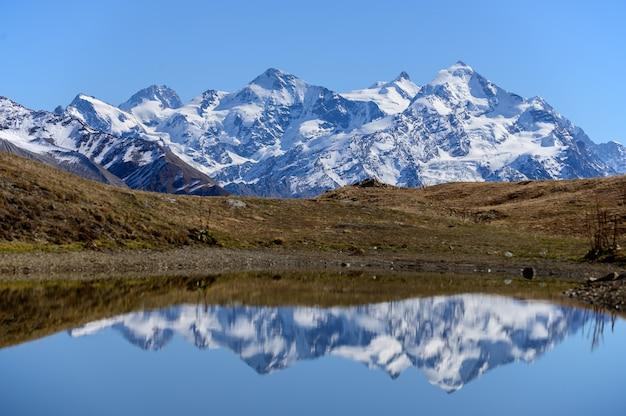 Jezioro koruldi w swanetii, gruzja. odbicie lustrzane w wodzie. widok na góry kaukazu