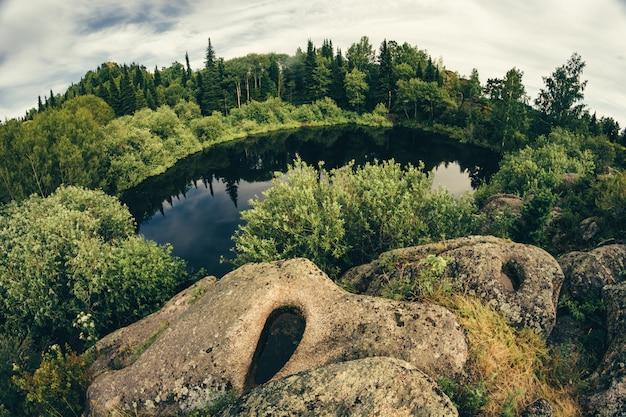 Jezioro na szczycie wzgórza, otoczone skałami i zaroślami, uchwycone przez obiektyw typu rybie oko.