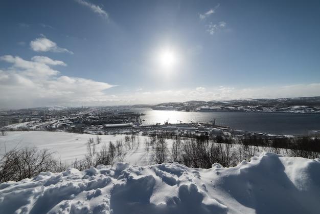 Jezioro na tle zaśnieżonego pola w słoneczny dzień