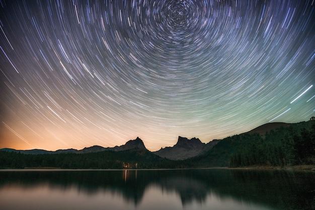 Jezioro nocą z niesamowitym gwiaździstym niebem i gwiazdowymi śladami z odbiciami w wodzie.