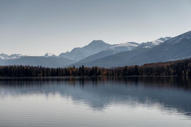 Jezioro ostrosłupowe z pasmem górskim i odbiciem czystego nieba w parku narodowym jasper, kanada