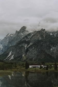 Jezioro otoczone drzewami i górami skalistymi pokrytymi mgłą pod zachmurzonym niebem