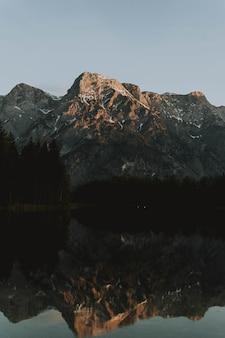Jezioro otoczone górami z drzewami odbijającymi się w wodzie w ciągu dnia