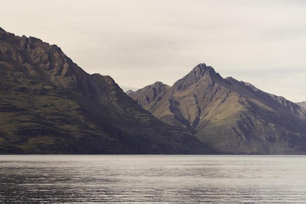 Jezioro otoczone skałami pod słońcem w nowej zelandii