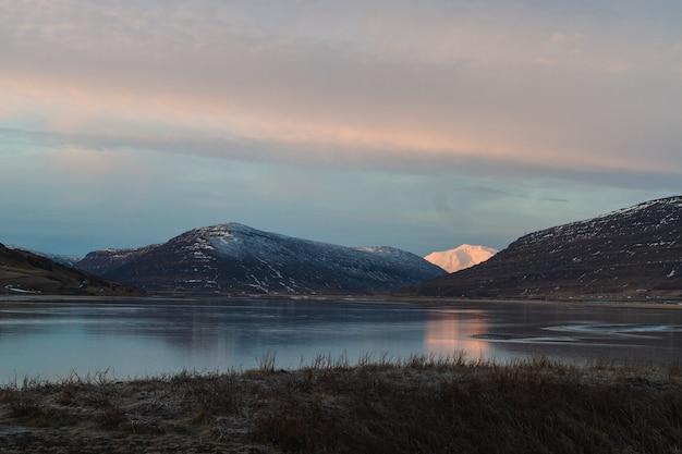 Jezioro otoczone wzgórzami pokrytymi śniegiem odbijającym się w wodzie podczas zachodu słońca na islandii