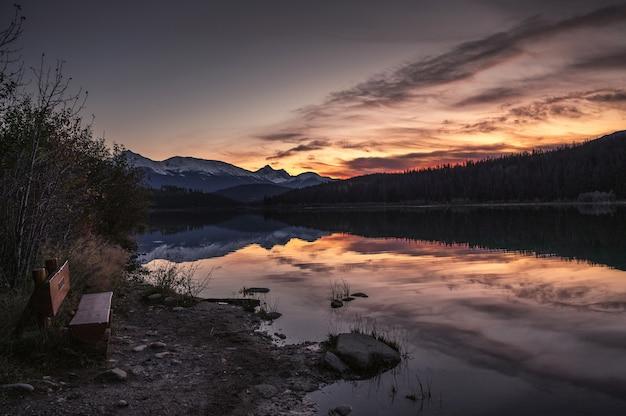 Jezioro patricia z pasmem górskim i zachodem słońca w parku narodowym jasper, kanada