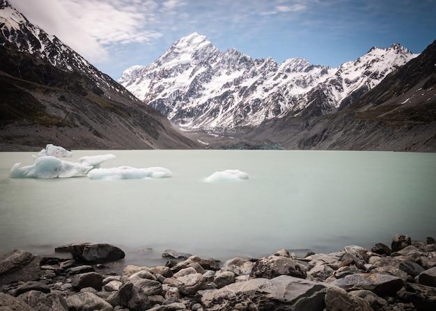 Jezioro polodowcowe z kawałkami lodu unoszącymi się na wodzie ze szczytem górskim w tle