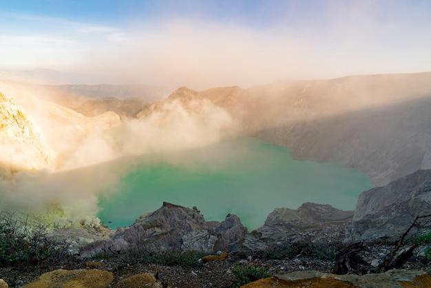 Jezioro pośrodku skalistego krajobrazu wyrzucającego dym