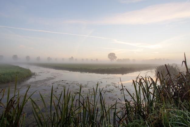 Jezioro pośrodku trawiastych pól z mgłą o zachodzie słońca