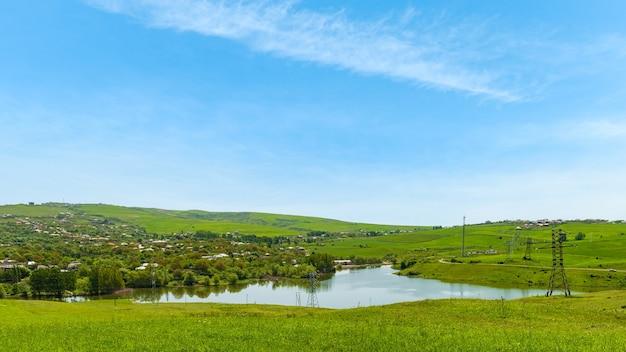 Jezioro przy wiosce z zielonymi wzgórzami