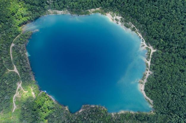 Jezioro w gęstym lesie sosnowym z lotu ptaka