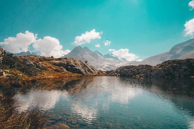 Jezioro w pobliżu góry pod błękitnym niebem w ciągu dnia