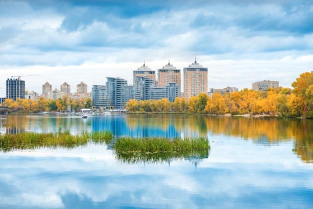 Jezioro z błękitną wodą, jesienny żółty las i wysokie budynki na drugim brzegu