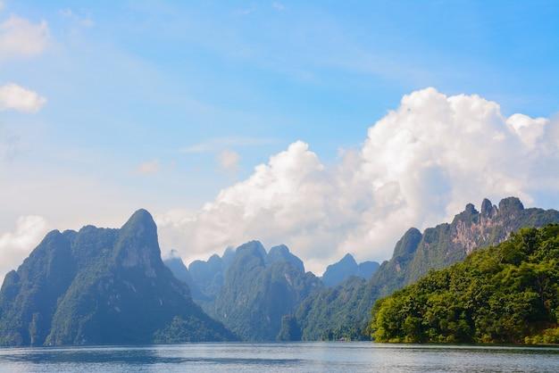 Jezioro z górami i lasem i krajobrazem zachmurzonego nieba