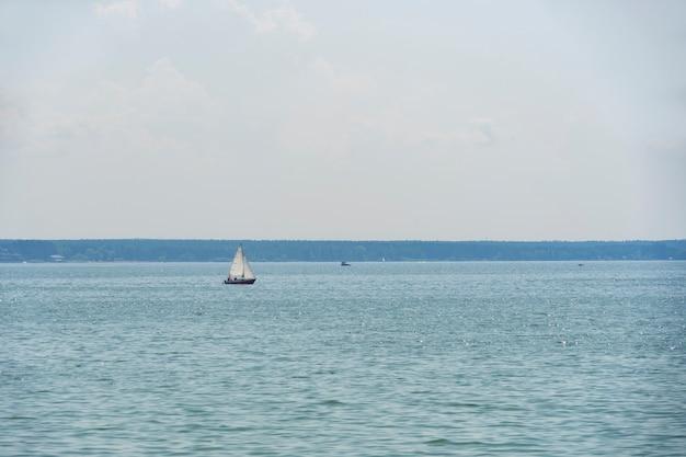 Jezioro z małą łódką rano w lecie.