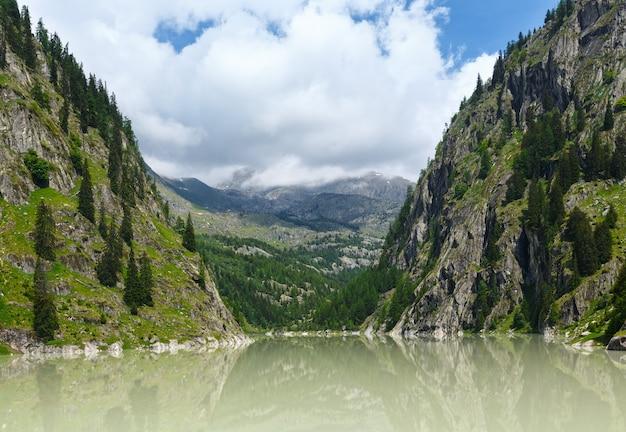 Jezioro z mętną wodą utworzyło tamę. letni krajobraz górski (alpy, szwajcaria)
